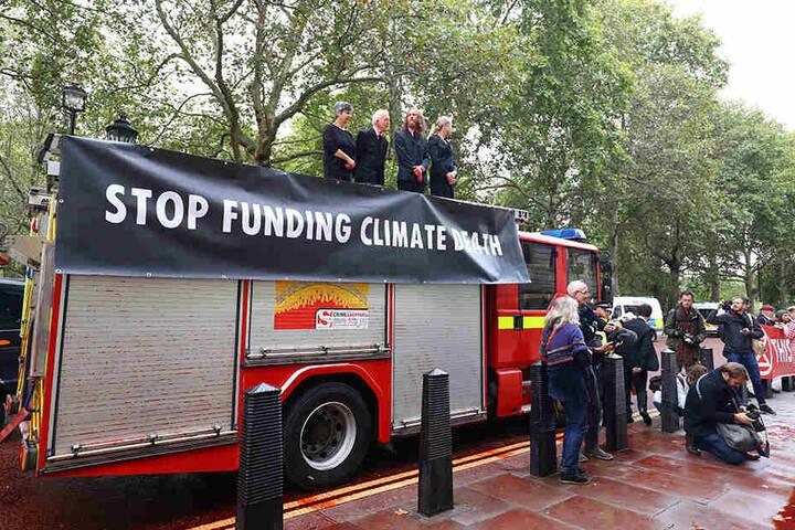 """Die Klima-Aktivisten der Gruppe """"Extinction Rebellion"""" stehen auf dem ausrangierten Feuerwehrauto."""