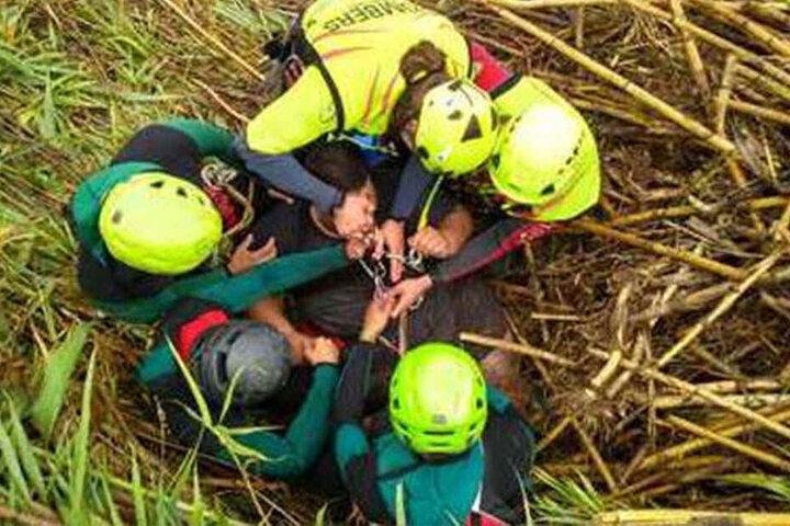 Feuerwehrleute und Beamte der Guardia Civil binden einen Mann mit einem Klettergurt, um ihn aus einem überquellenden Fluss in Canals, Valencia, zu holen.