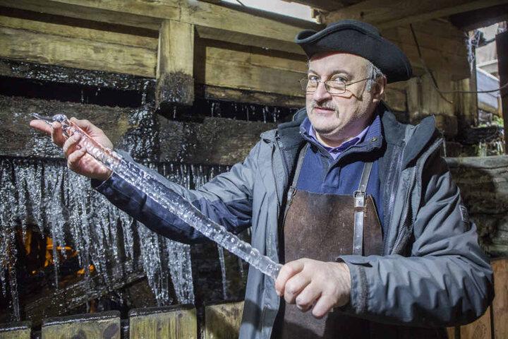 Bernd Schreiter (54, Museumsführer Frohnauer Hammer) mit den Eiszapfen am Wasserrad.