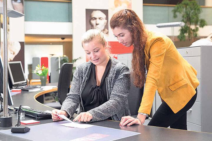 Cindy (21) lässt sich von Serviceberaterin Lisa Fröde (25) erklären, worauf sie bei Überweisungen achten muss.