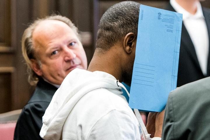 Der Angeklagte versteckt sein Gesicht hinter einer Mappe.