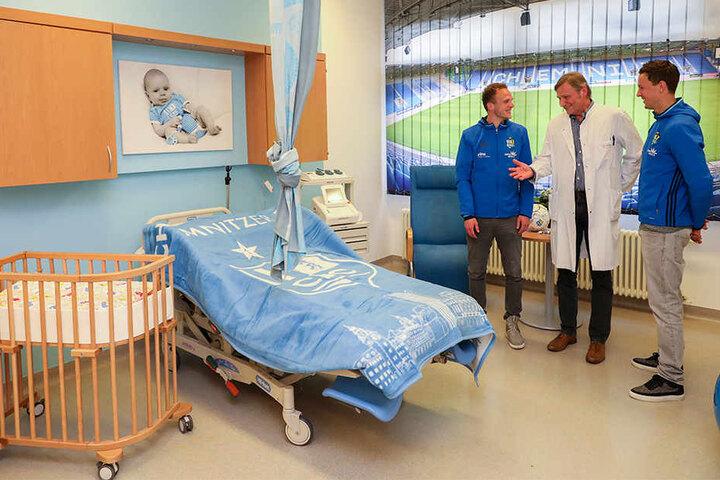 Lutz Kaltofen (M), Chefarzt der Klinik für Frauenheilkunde und Geburtshilfe, erläutert den beiden CFC-Profis Julius Reinhardt (l) und Tim Danneberg den neuen Kreißsaal.