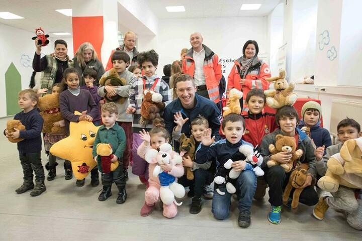Eislöwe Brendan Cook (Mitte) im kreis vieler Flüchtlingskinder mit ihren neuen Spielkameraden.