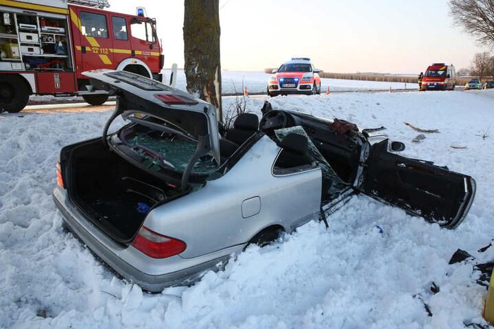 Ein demoliertes Fahrzeug, mit dem eine Familie verunglückte, steht nach einer Kollision mit einem Baum im Schnee neben der Bundesstraße 465.