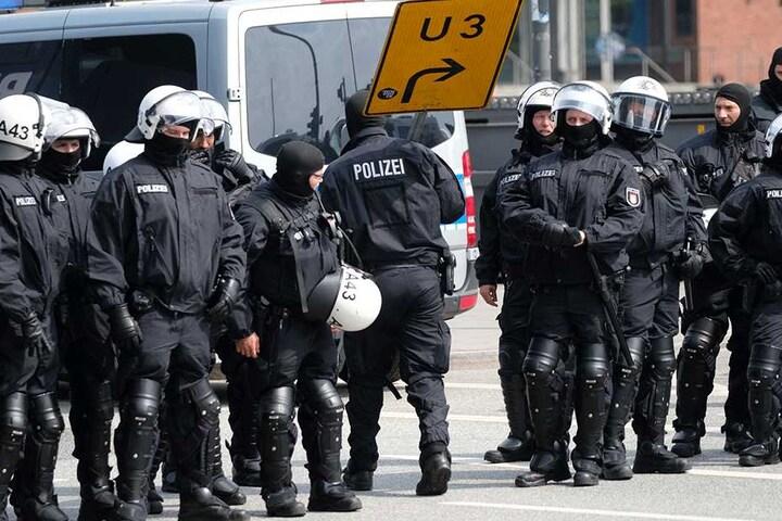 Polizisten entfernen am Baumwall in Hamburg alle losen Gegenstände, die von Demonstranten als Wurfgeschosse verwendet werden könnten.
