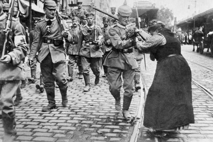 Waffenstillstand 1918: Eine Frau übergibt einen Blumenstrauß an preußische Soldaten, die Berlin verlassen, um an die Front zu ziehen.