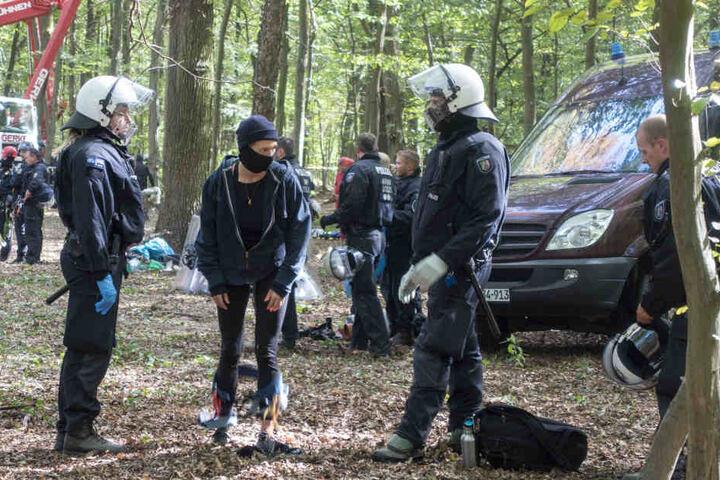 Polizeibeamte mit einem Aktivisten im Wald.