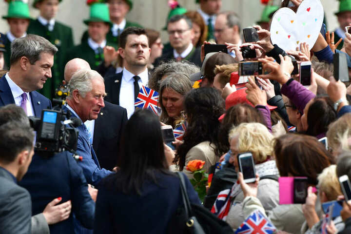 Der britische Thronfolger Prinz Charles (M l) begrüßt die Menschen neben dem bayerischen Ministerpräsidenten Markus Söder (l, CSU) bei seiner Ankunft vor der historischen Residenz auf dem Max-Joseph-Platz.