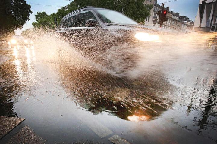 Ein Auto fährt durch eine Pfütze: Ein Bild, an dass sich die Hessen in den kommenden Tagen gewöhnen müssen.