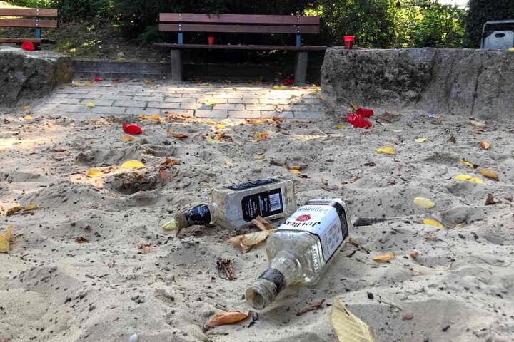 Flaschen und Becher verteilen sich im Sand.