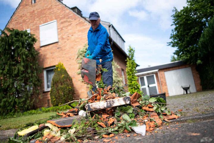 Ein Anwohner schüppt in Boisheim die Trümmer seines Hauses zusammen.