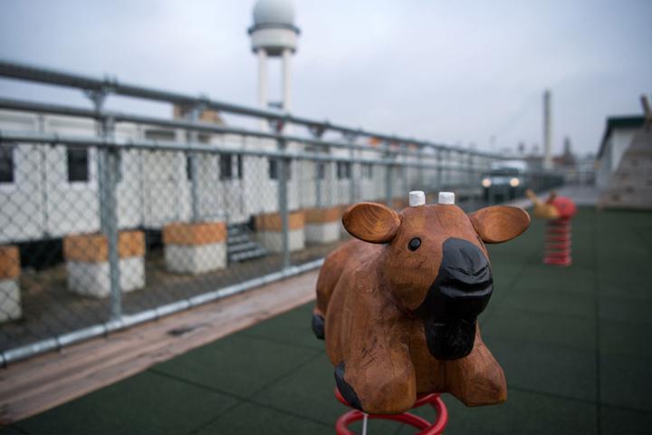 Eine Wippe steht auf einem Kinderspielplatz vor einigen der fast 900 Container auf dem Gelände.
