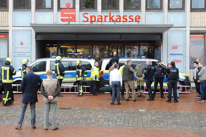 Einsatzkräfte der Polizei und Feuerwehr verbarrikadierten den Eingang einer Sparkassen-Filiale in Heide mit ihren Fahrzeugen.