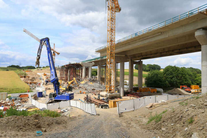Bagger ziehen an der eingestürzten Talbrücke Schraudenbach an der Autobahn A7 herabgestürzte Teile auseinander (Archivbild).