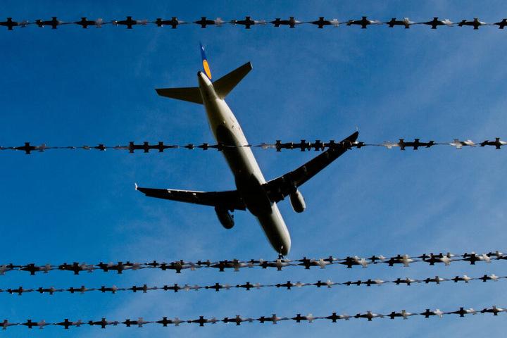 Ein Flugzeug fliegt über einen Stacheldrahtzaun. (Symbolbild)