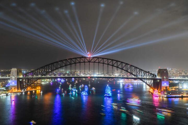 Diese Langzeitaufnahme zeigt Schiffe, die am Ende der Silvesterfeierlichkeiten unter der festlich beleuchteten Harbour Bridge durchfahren.