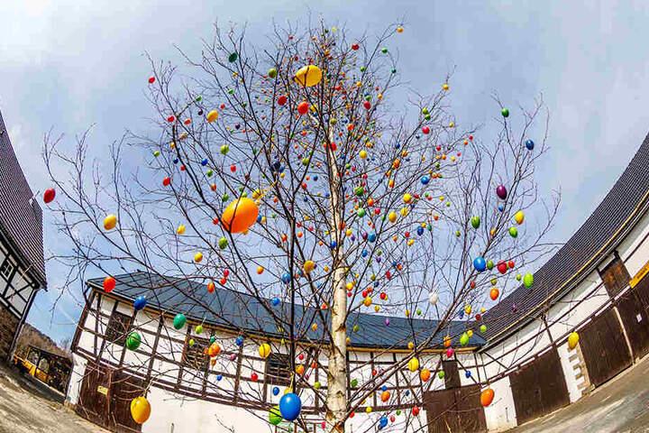 Ein geschmückter Eier-Baum und ein schöner Osterbrunnen zieren den Innenhof des Weidegutes.