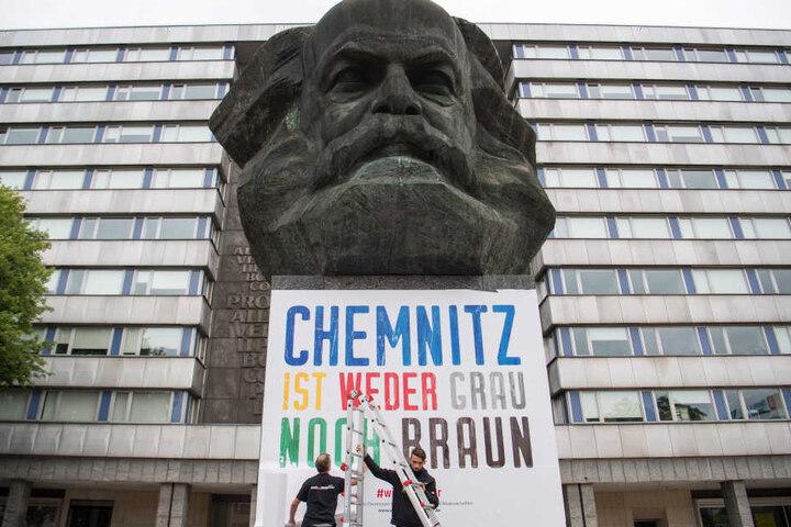 """Zwei Männer befestigen am Karl-Marx-Denkmal ein Plakat mit der Aufschrift """"Chemnitz ist weder grau noch braun""""."""