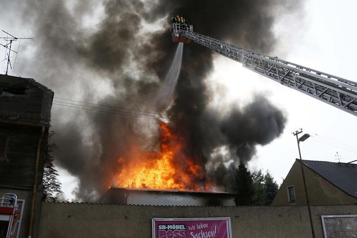 Die Flammen schlagen durch ein Dach.