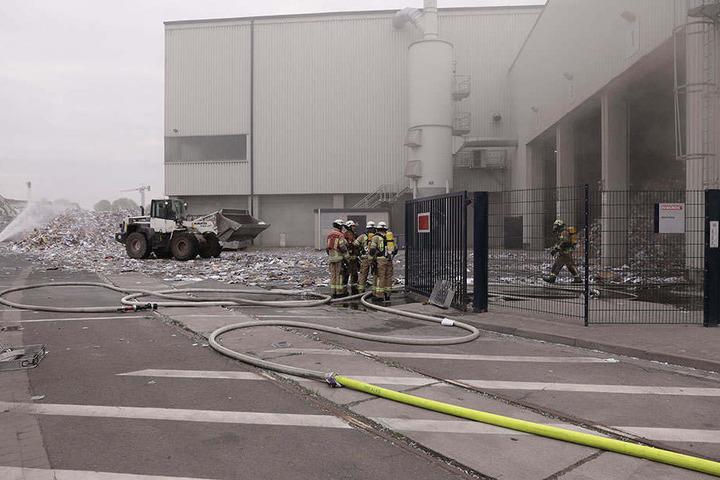 Einsatzkräfte besprühen das brennende Altpapier.