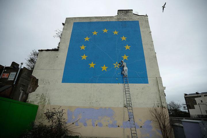 Ein Wandgemälde des Künstlers Banksy zeigt eine EU-Flagge mit einem Handwerker, der einen der Sterne abschlägt.