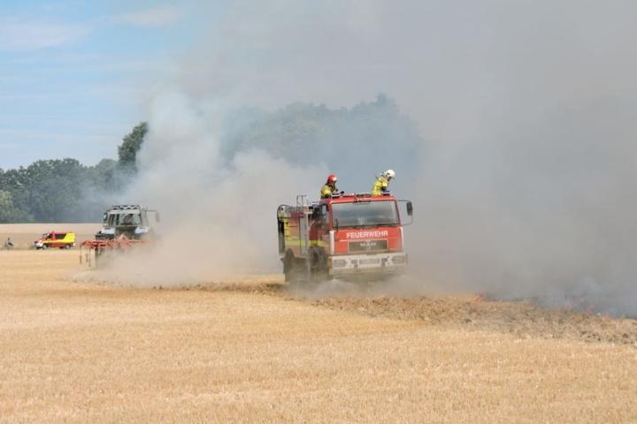 Zwei Feuerwehrmänner löschen die Flammen in Kössern von oben.