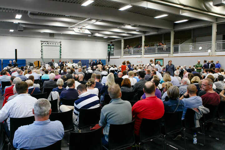 Einwohner der Gemeinde Boostedt sitzen während einer Bürgerversammlung in einer Sporthalle.