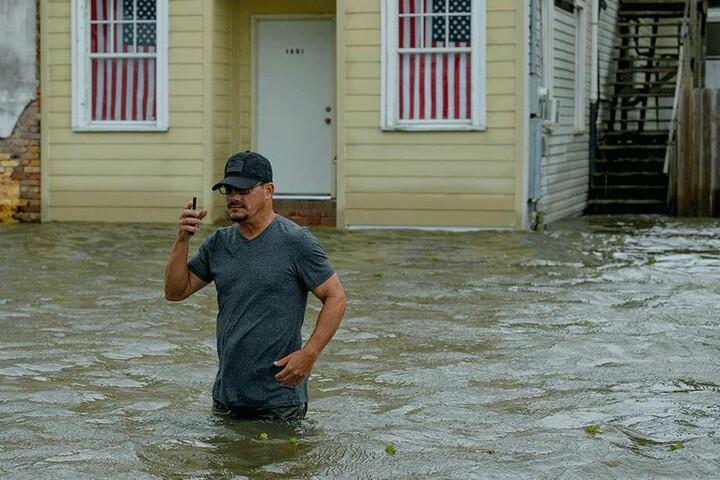 Barry Williams telefoniert, während er durch hüfthohes Wasser im Ort Mandeville watet.