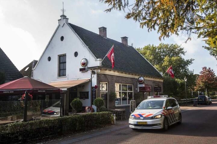 """Ein Polizeiwagen fährt an dem Café """"De Kastelein"""" vorbei. Auf einem zum Dorf gehörenden abgelegenen Hof soll eine Familie jahrelang im Keller gehaust haben"""