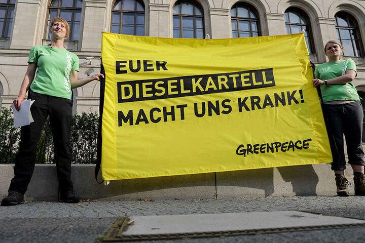 """Greenpeace-Aktivisten protestieren vor dem Bundesverkehrsministerium in Berlin mit einem Transparent """"Euer Dieselkartell macht uns krank!""""."""
