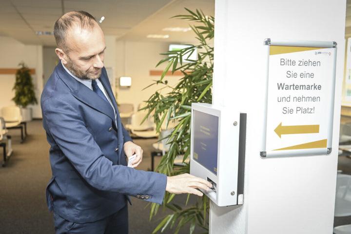 Der Geschäftsführer des Jobcenters Pierre Ullmann (49) testet den neuen Automaten für Wartemarken.