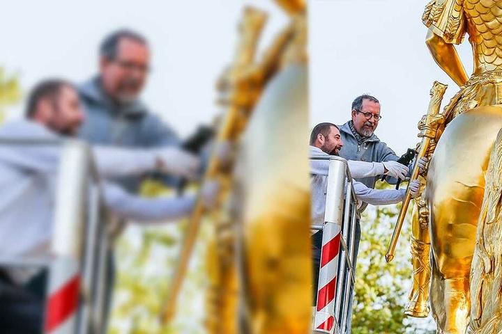 Restaurator Harald Straßburger (64, r.) und Klempnermeister Lars Knoblich (41) befestigen das reparierte Schwert. Mit einem Schaft verstärkt, soll es einer neuen Kletterattacke trotzen.