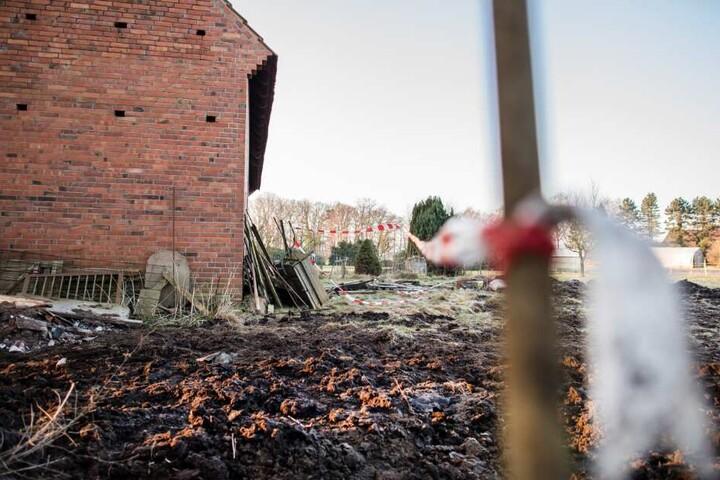 Ein Absperrband hängt an der Rückansicht des Hofes, auf dem am 09.03.2018 eine der drei Leichen gefunden wurde.