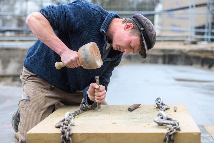 Steinmetzgeselle Georg Ahner (25) meißelt das Firmenlogo in den Schlussstein der neuen Gewölbe.
