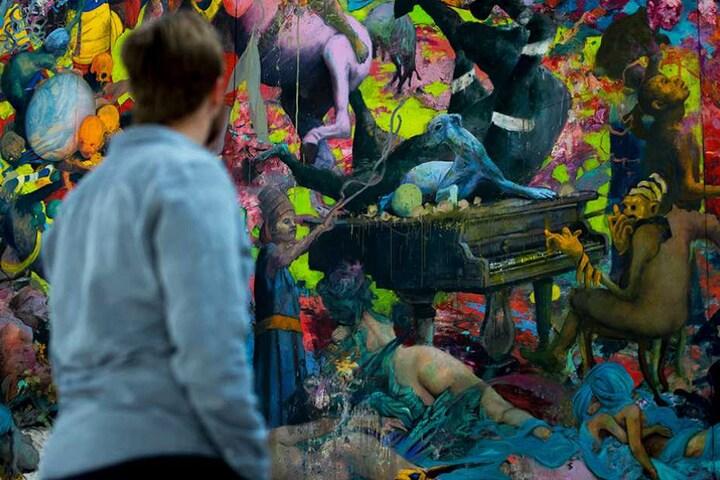 """Ein Besucher steht vor dem Gemälde """"Zeitlaich"""" des Berliner Künstlers Jonas Bungert."""