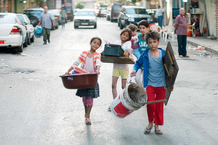 Zain (vorne-rechts., Zain Al Rafeea) mit seinen Geschwistern beim Tragen und Verkaufen von Sachen auf der Straße.