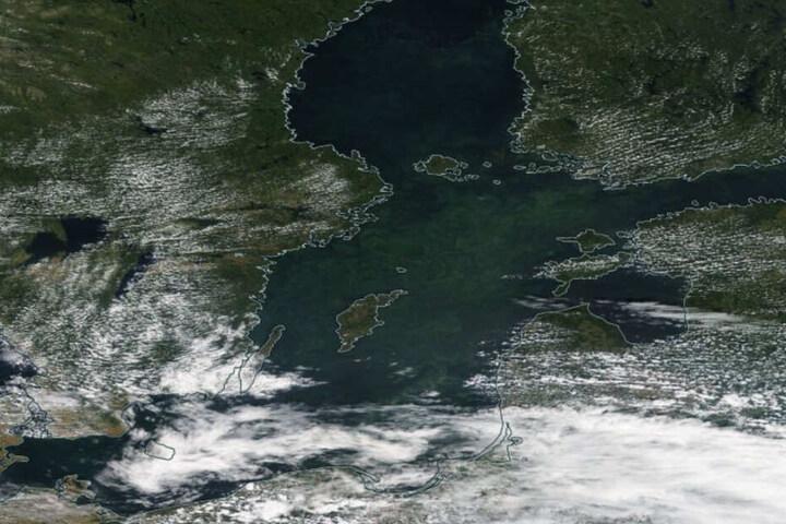 Vor der Küste Skandinaviens ist ein grünlicher Schleier zu erkennen.