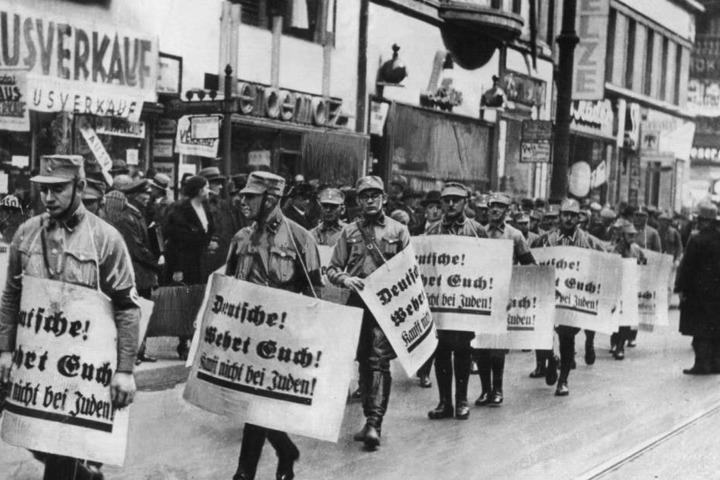 """""""Deutsche wehrt Euch! Kauft nicht bei Juden!"""" steht auf den Schildern, die Männer der SA bei einem Hetzmarsch gegen Juden durch die Straßen Berlins tragen."""