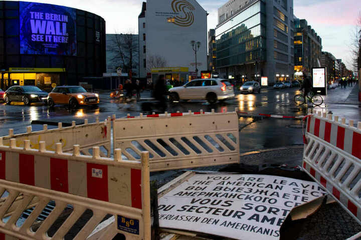 Die beschädigte Replik des berühmten Schildes am Checkpoint Charlie liegt nach dem Sturm auf der Straße.