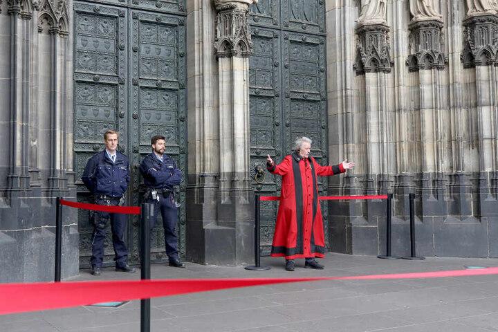 Ein Domschweizer vor dem Zugang zum Kölner Dom.