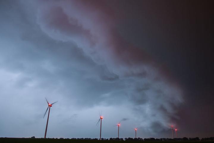 Eine Gewitterzelle zieht in der Nacht über die Landschaft mit einem Windenergiepark im Landkreis Oder-Spree.
