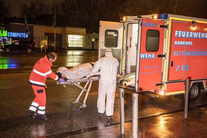 Sanitäter bringen einen der Bewohner in einen Rettungswagen.