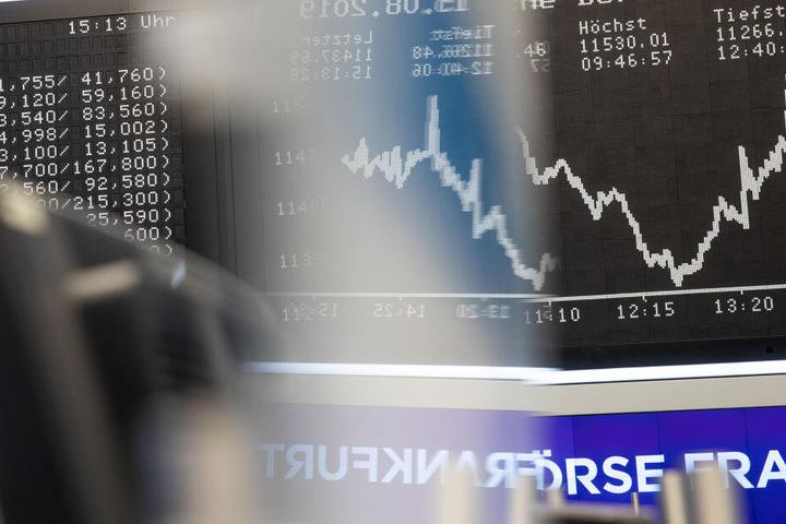 Die Dax-Kurve (r) spiegelt sich im Handelssaal der Börse in dem Firmenschild (M) von Händlern.