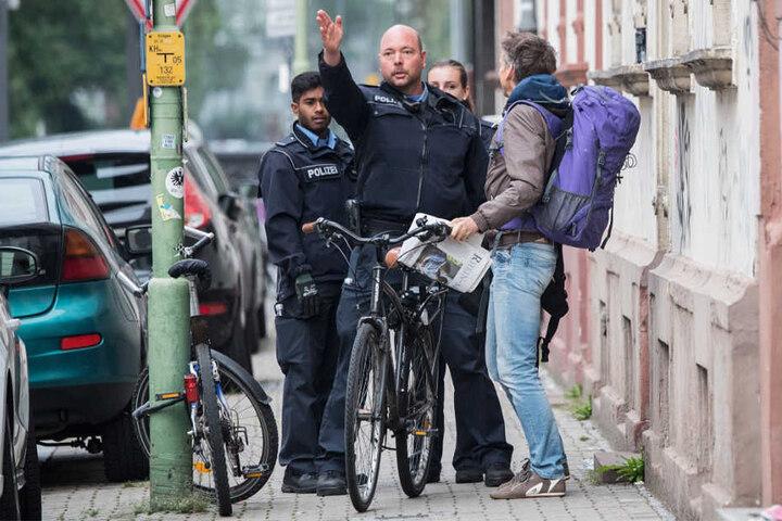 Zwei Polizisten und zwei Anwohner unterhalten sich im Sperrgebiet Frankfurt-Westend.