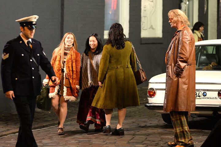 Die Schauspieler und Komparsen tragen zeitgemäße Kleidung aus den 70er Jahren.