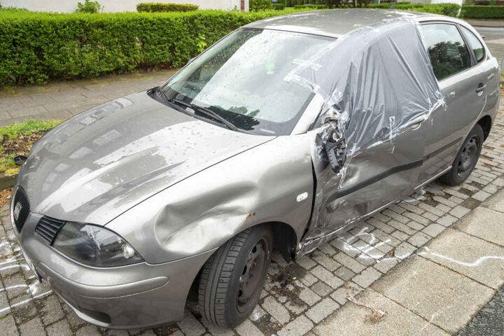 Ein durch den Unfall beschädigtes geparktes Fahrzeug steht am Straßenrand.
