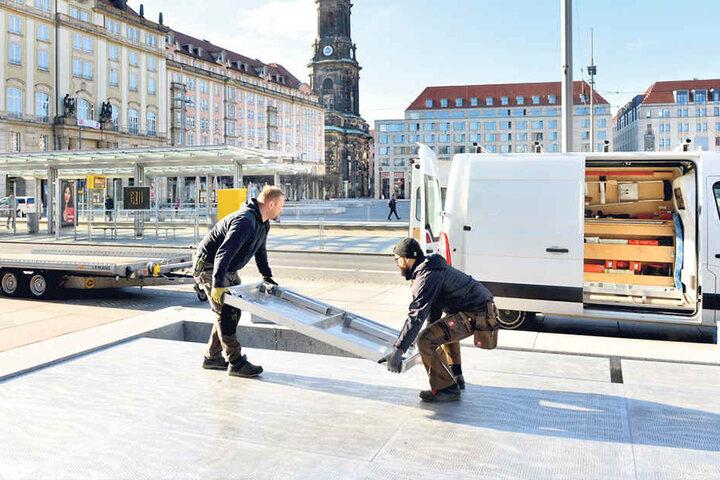 Winter adé! Frank Dietze (41, li.) und Sebastian Stephan (28) von der Holzwerkstatt Dietze decken den Brunnen vorm Kulturpalast ab.