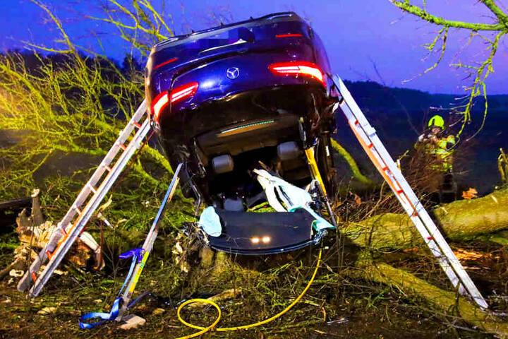 Das Auto blieb auf dem Dach in einer Baumgruppe liegen.