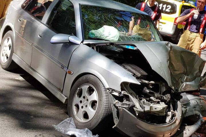 Einsatzkräfte betrachten das beschädigte Auto.