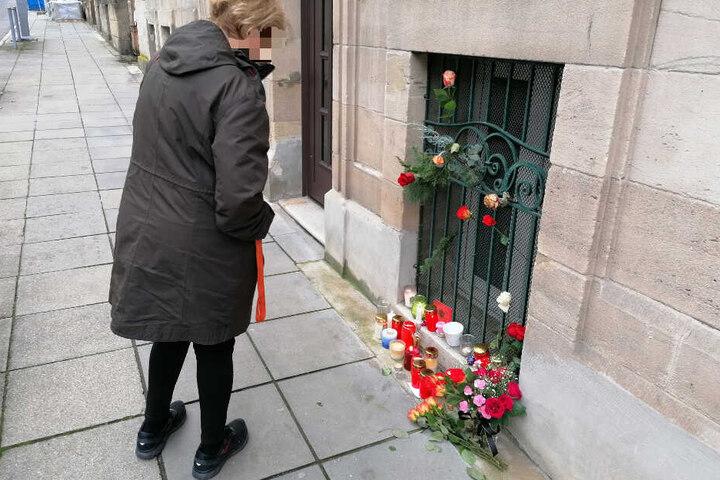 Eine Frau bleibt an der Stelle stehen, an der Menschen der Toten gedenken.